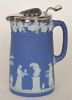 A late 19th Century Wedgwood Jasperware water jug with silver plated cover, the body with low relief classical scenes against a dark blue ground, impressed marks, height 16cm