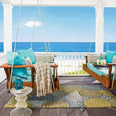 A patterned rug makes this cozy porch one the beach even more inviting. coastalliving.com