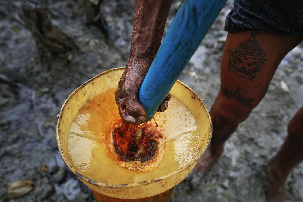 Ko Min, 26, extrae manualmente el aceite de una de las tres 300 pies pozos profundos en los que trabaja en el municipio Minhla del distrito ...