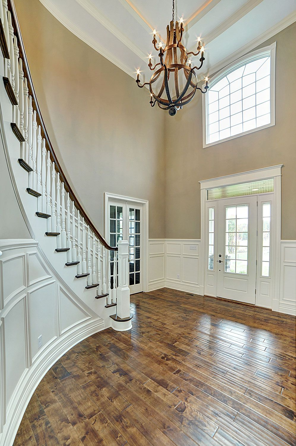 Curved staircase in two story foyer with white wainscoting for Foyer staircase ideas