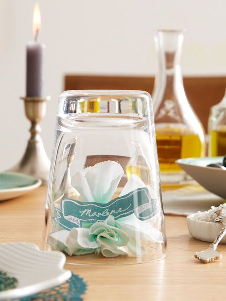 Diese kleine Deko-Idee dient als Tischkärtchen. Sie brauchen dafür nur einen Streifen weißen Baumwollstoff, Batikfarbe, etwas Tonpapier und Bastellaune!
