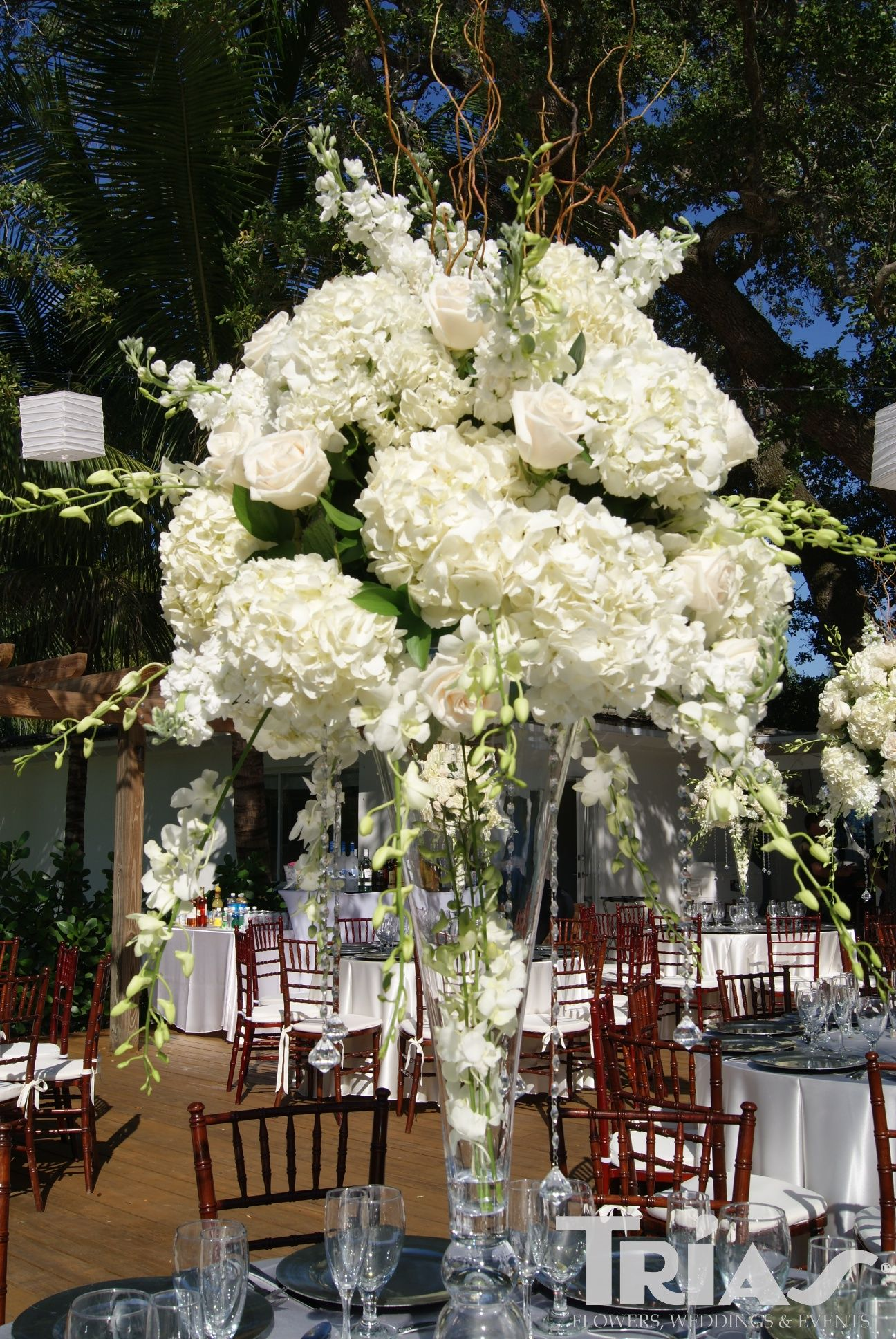 Tall centerpiece with white hydrangeas, roses, and orchids