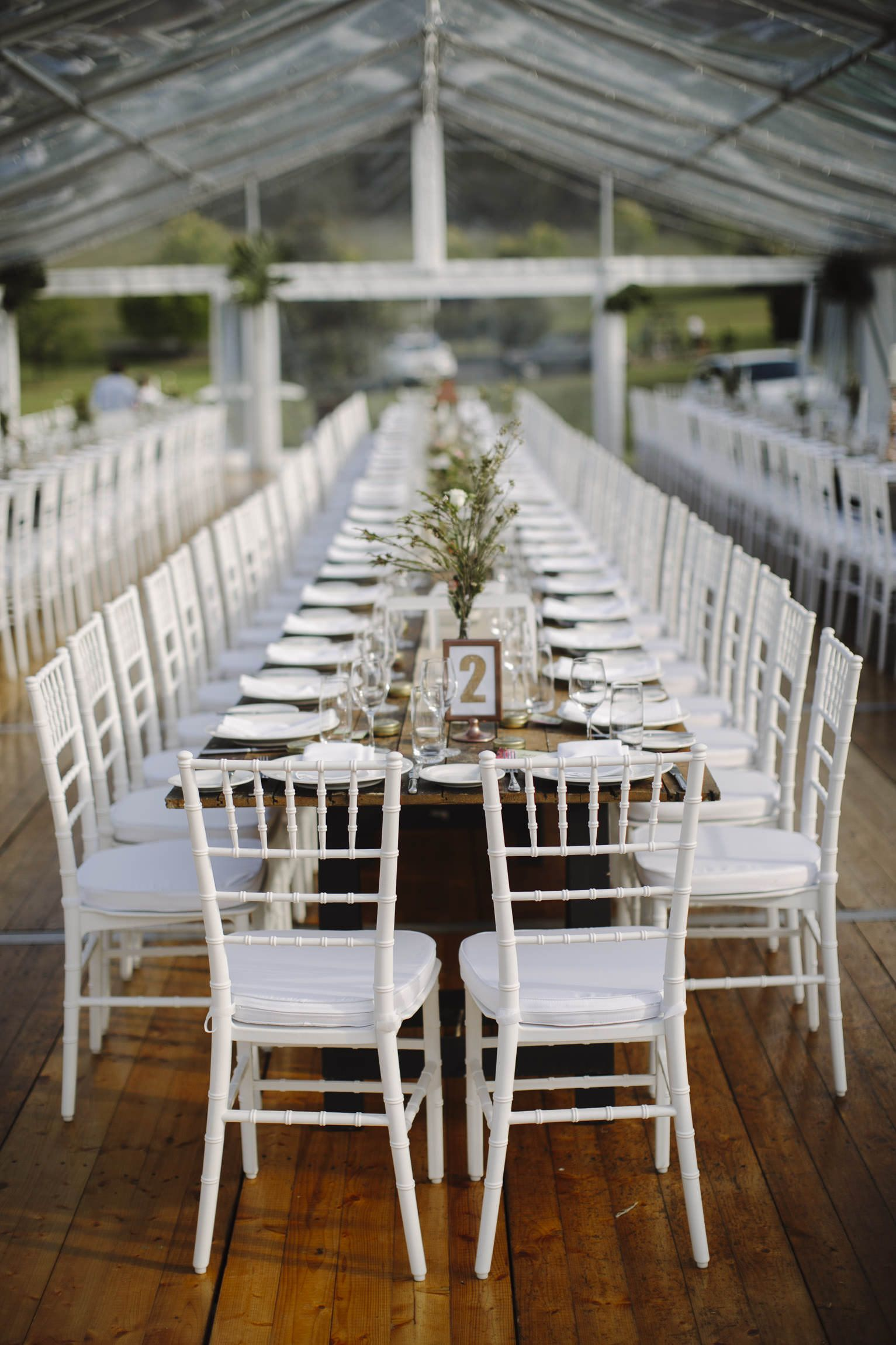 white tiffany chairs marquee structure integrated timber flooring