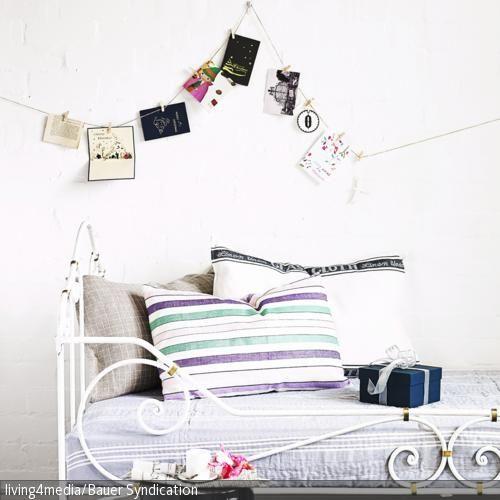 Neben einem Metallbett im Shabby-Look ist die gespannte Schnur mit Postkarten eine witzige Dekoidee, die vor der weiß getünchten Wand besonders gut hervorsticht. - mehr auf roomido.com