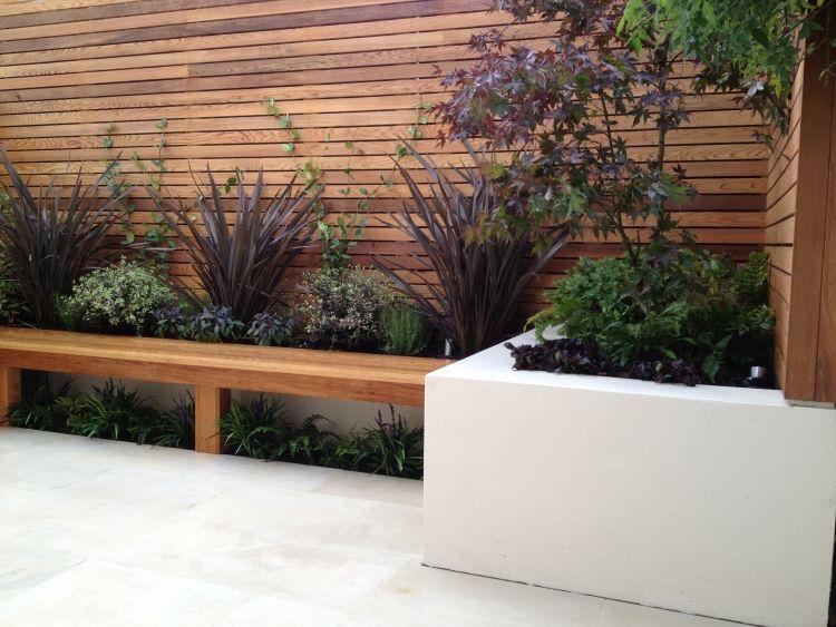 sichtschutzzaun und sitzbank aus holz  hochbeete mit pflanzen