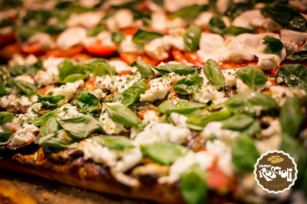 Pizza Caprese. It has the same dough of the white one, but it is spiced with tomatoes slices, fresh mozzarella, oregano and basil