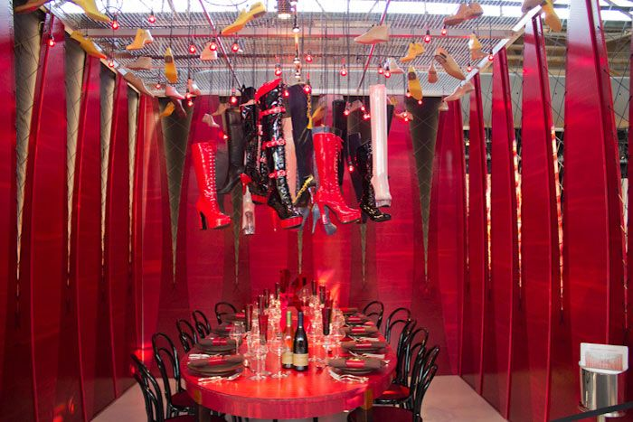 A chandelier of patent leather boots and corset wall for Broadway bedroom ideas