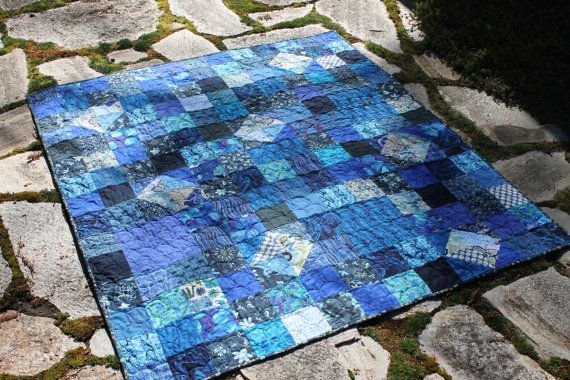 """If blue is your favorite color, this is the perfect quilt for you. So many pretty shades of blue can be found in this wonderful quilt. From navy blue to a bright happy turquoise! Happy diamonds of light fabrics give the quilt great interest.  The quilt measures 53"""" x 59"""". It is backed with a wonderful turquoise fabric. A fun loopy stitch is quilted in a navy blue thread."""