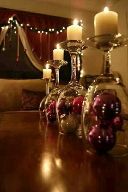 Wine glasses with glass tree ornaments under them used as candle holders.