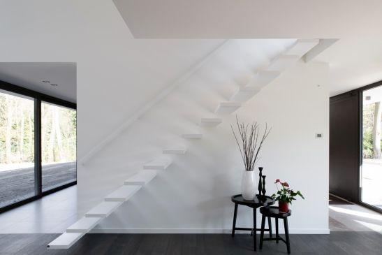 Zwevende trap met corian treden en strakke leuning langs de muur