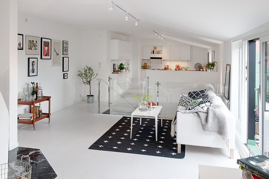 Clean Living Space Interior Style Of Swedish Apartment In White Beautified By Dark Patterned Area Rug On Family Room Area