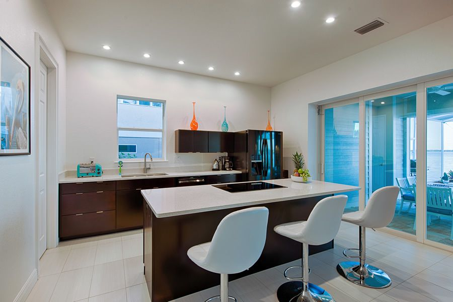 Coastal kitchen area with island ~ Lazy Tree luxury villa vacation rental in Cape Coral ~ Interior design by Julie Kuntz, Robb & Stucky Naples