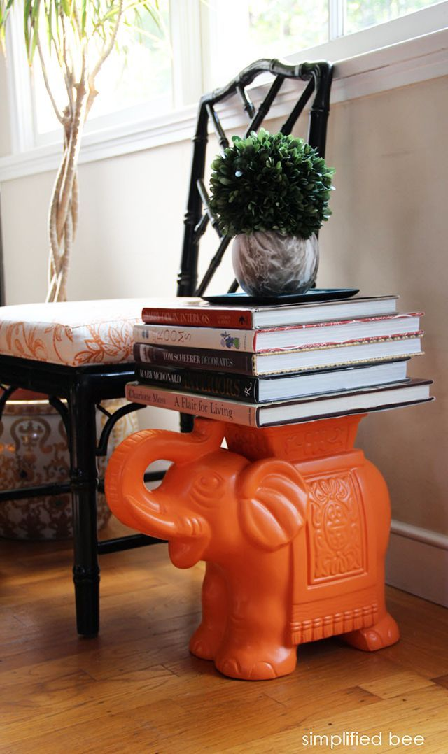 Coffee Table Books Stacked On An Orange Ceramic Elephant Garden Stool Act  As An End Table