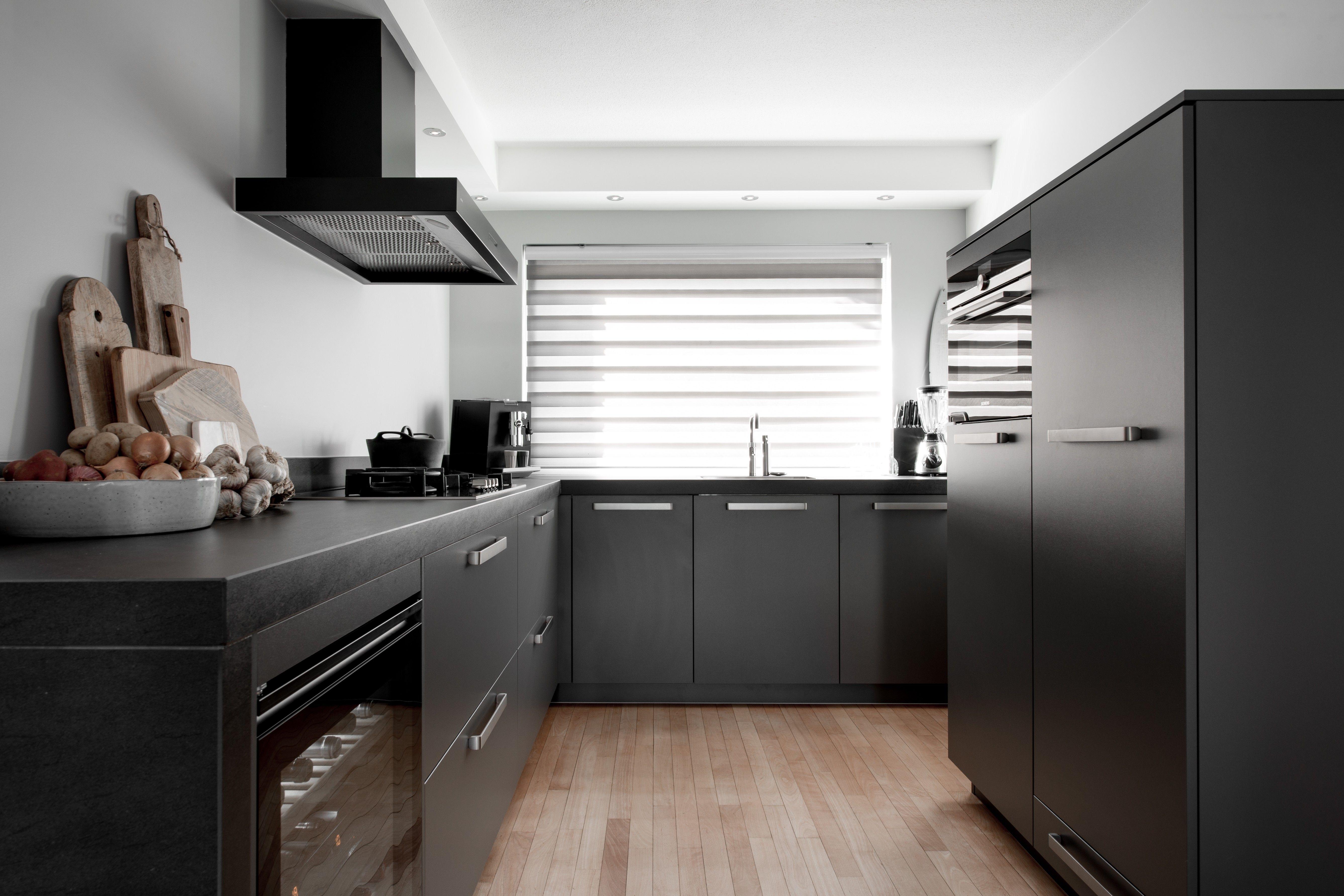 Keukenkasten Met Apparatuur : Een donkergrijze keuken met witte wanden zwarte apparatuur en een