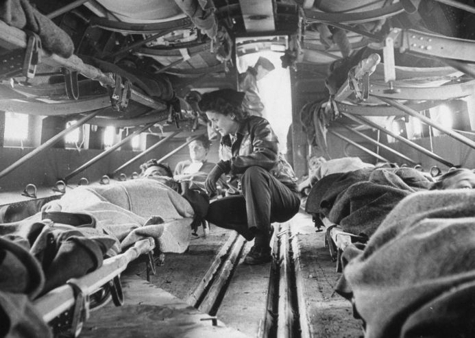 """Somewhere over North Africa an American """"flying nurse,"""" Second Lieut. Julia Corinne Riley, 23, checks on patients aboard a specially outfitted C-47 transport plane, used to ferry wounded men to hospitals, spring 1943."""