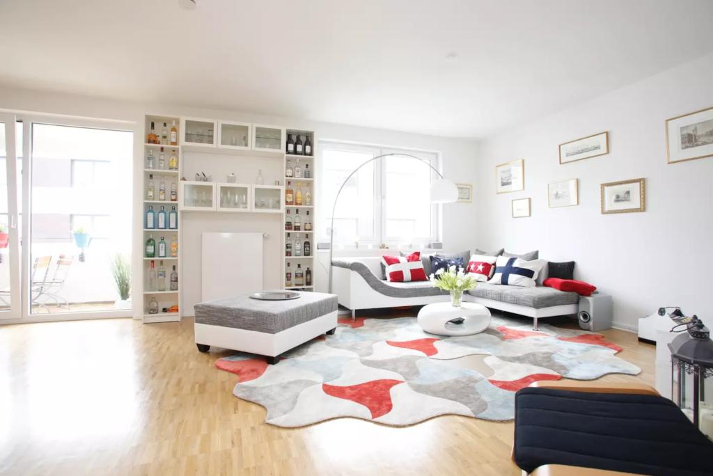 Großräumiges Wohnzimmer mit Parkett, großen Fenstern und einer ...
