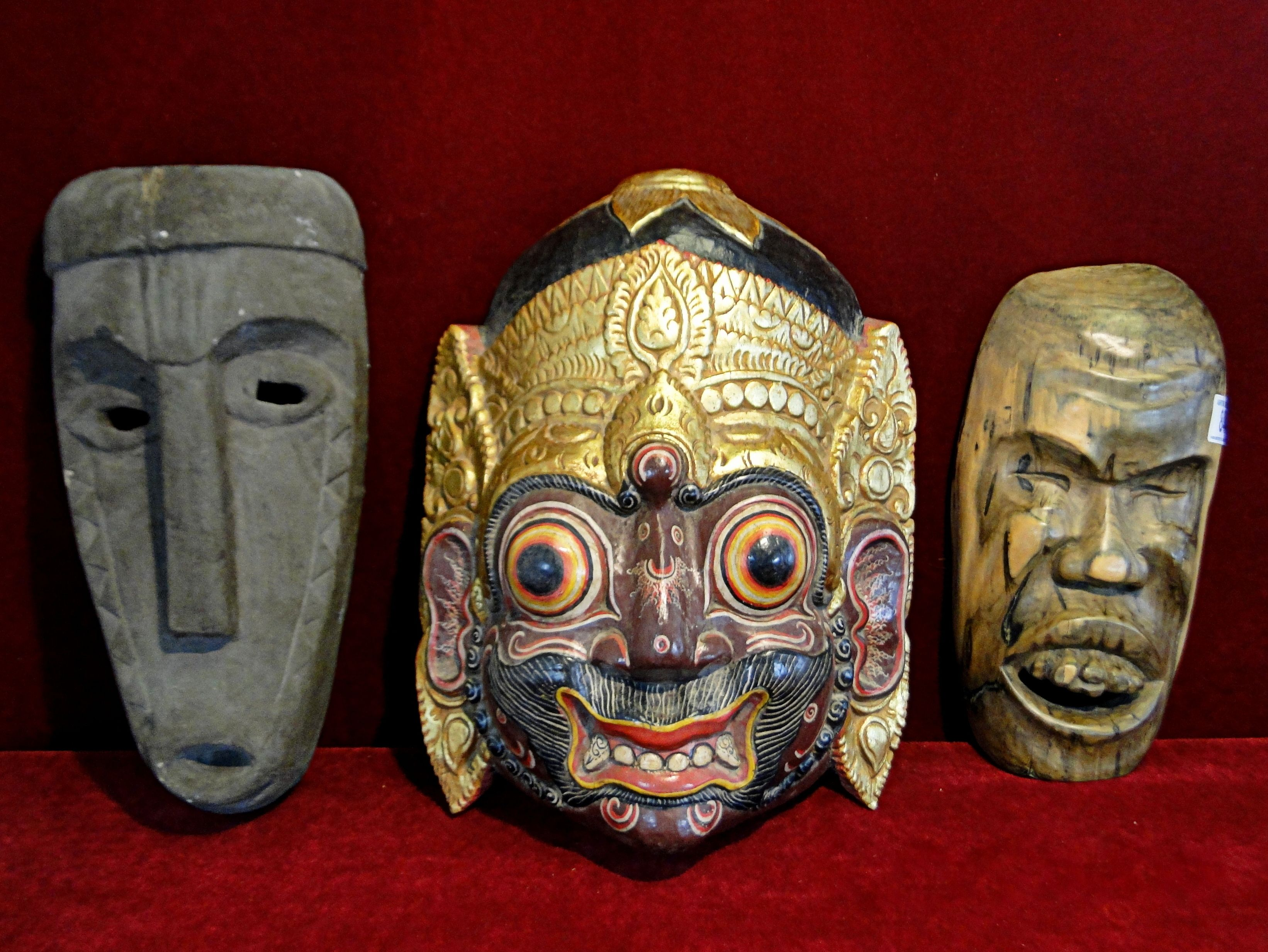 84) Large highly decorative painted Oriental hanging art mask, a cast hanging mask and a carved hardwood mask (3) Est. £30-£40
