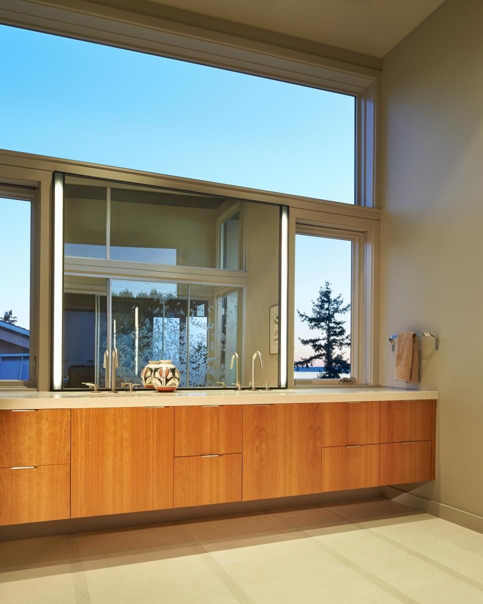 Floating Double Vanity With Thick Neutral Countertop Over Wood Cabinets and Windows Framing the Large Mirror