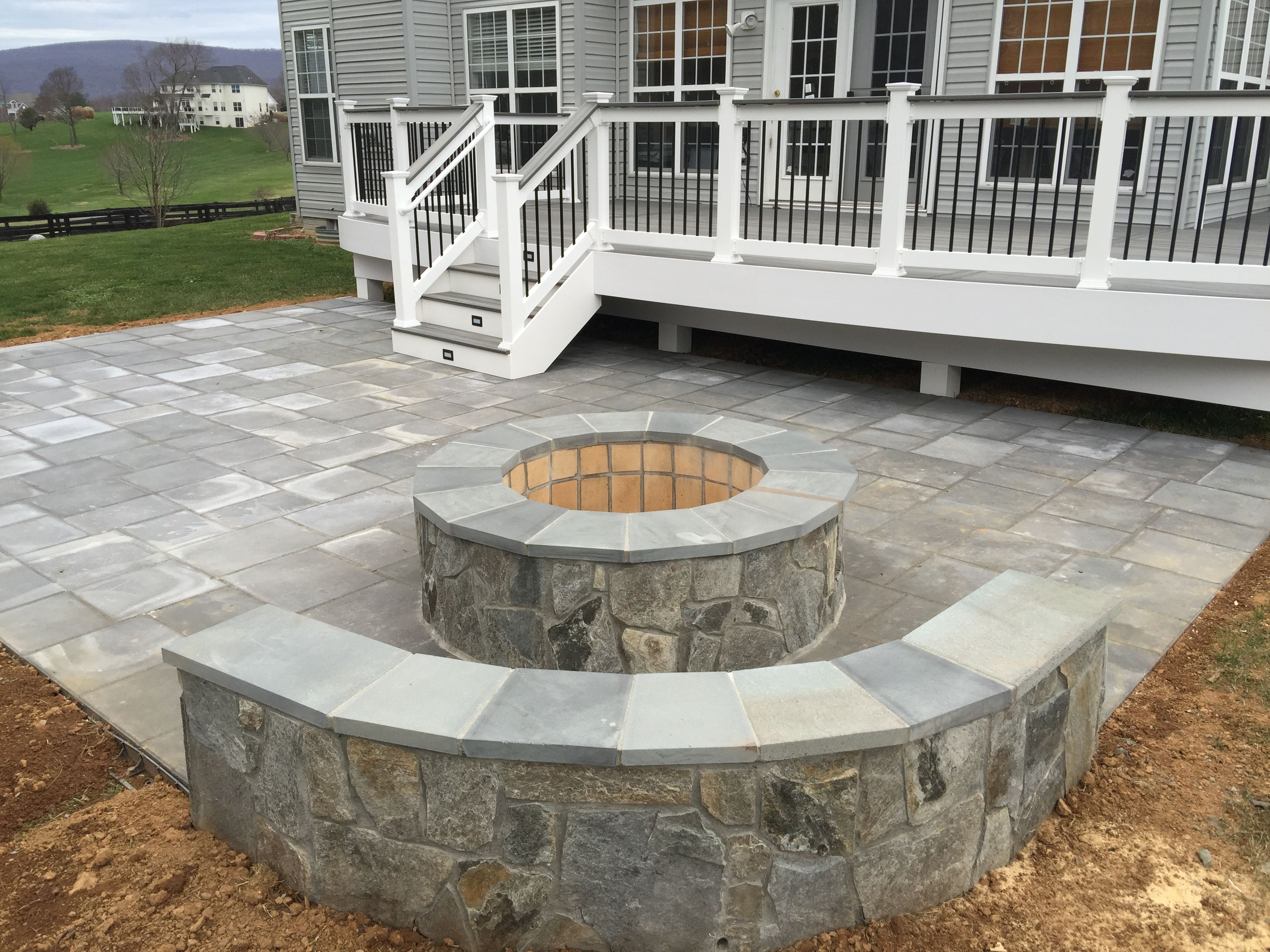 A Beautiful Paver Patio With Stone Seating Walls And Fire Pit Behind It Is Trex Deck Handrails White Vinyl Rails Black Aluminum Baers