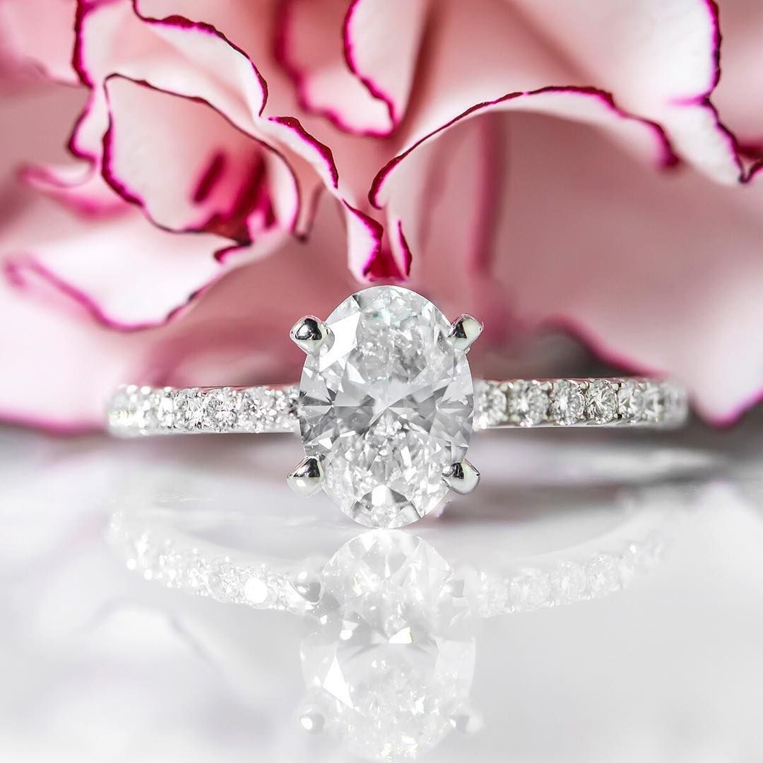 With a thin pave band and a stunning oval solitaire design, this ...