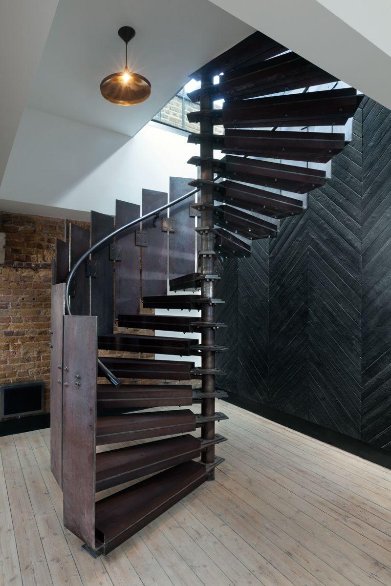 A spiral staircase and a charred wall at Tom Dixon's Metropolitan Wharf interior.