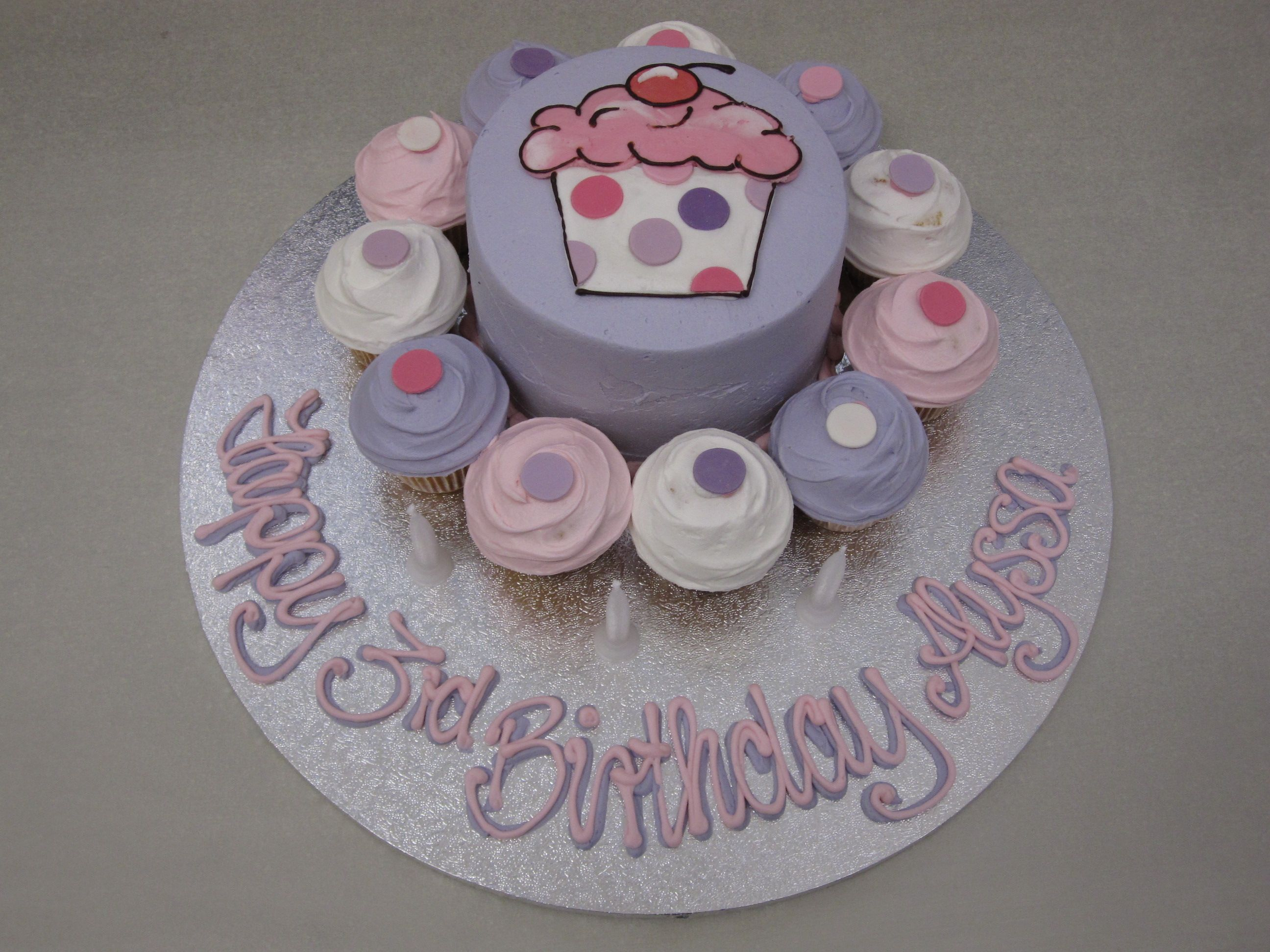 ... cake and mini cupcakes around, with inscription on a bigger board