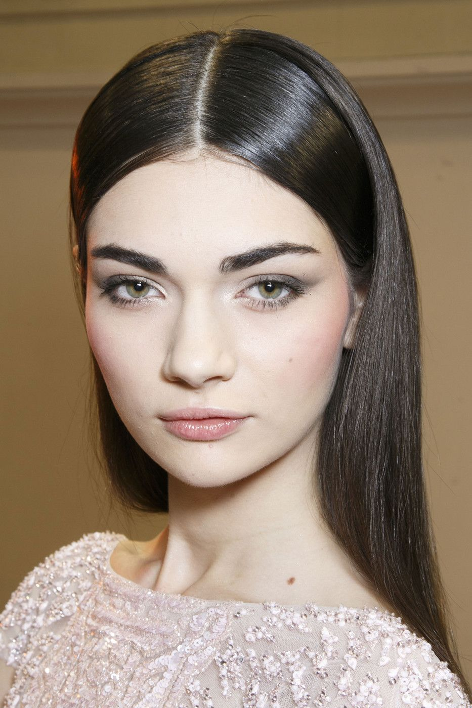 Pale skin sleek dark hair with center part bold brows gray shadow