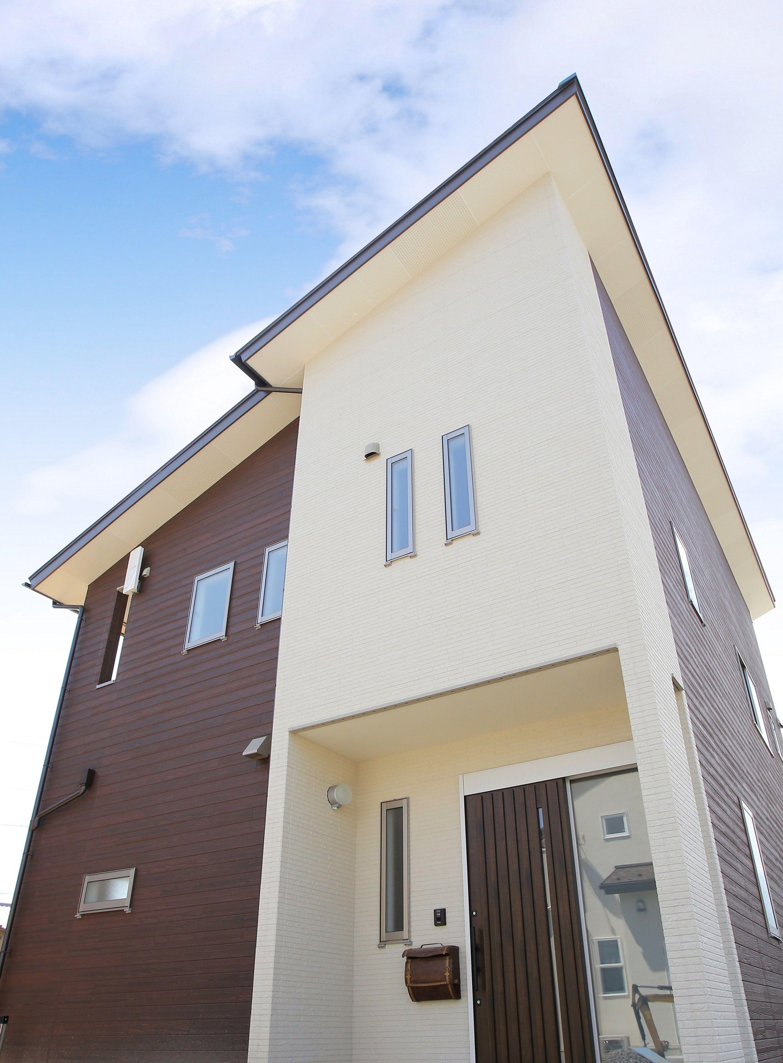 木目調の外壁に シンプルな白の外壁の組み合わせがおしゃれなお家