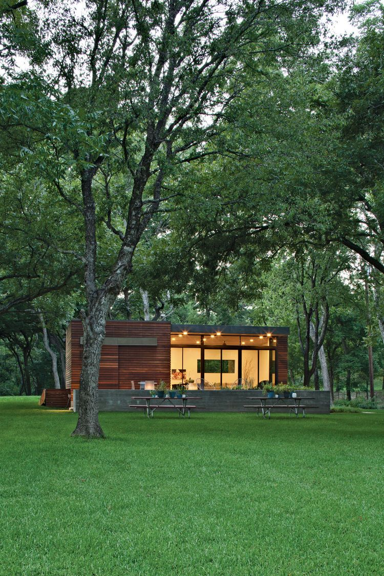 In a family s pint size lake retreat in austin texas ipe siding and decking meet concrete floors and steeland glass windows stained cyprus was used for
