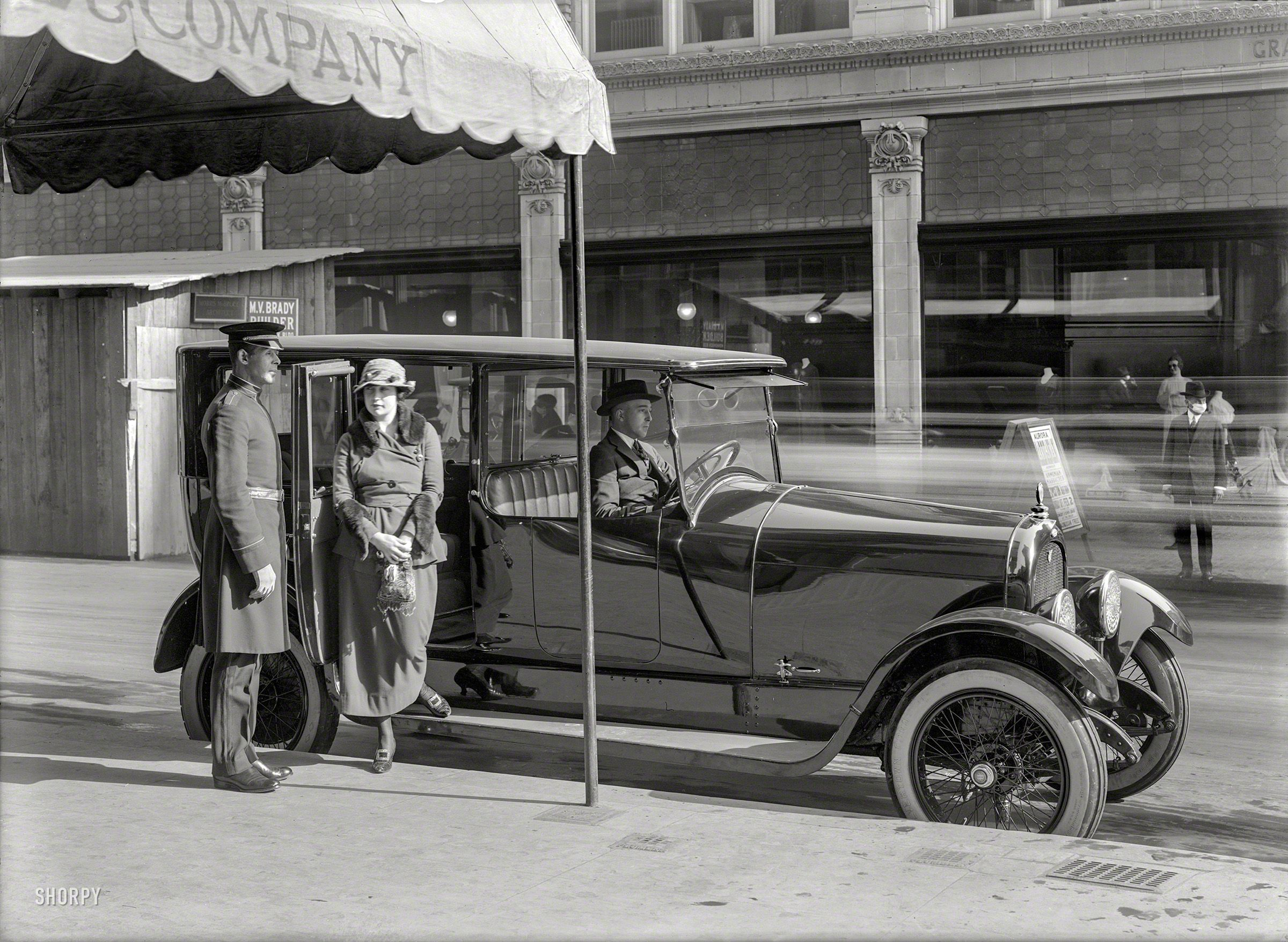 """Somewhere in San Francisco circa 1919. """"Woman alighting from Marmon limousine."""" At first this would seem to be all about the car, until we notice the pedestrian with the influenza face mask, and sign advertising what seems to be an appearance by the actress Aurora Mardiganian in connection with Aremnian Massacres"""