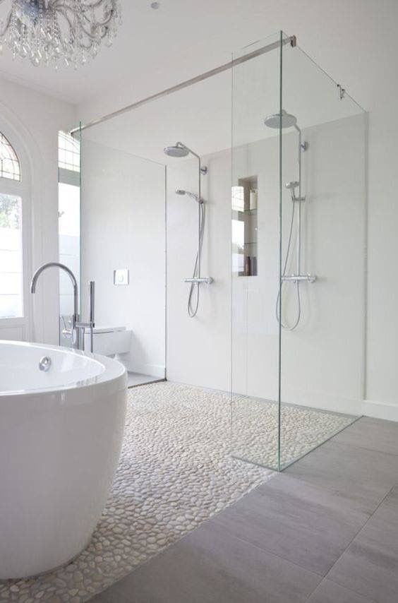 this luxury walk in shower enclosure has a frameless design that allows light to flow around the beautiful white bathroom