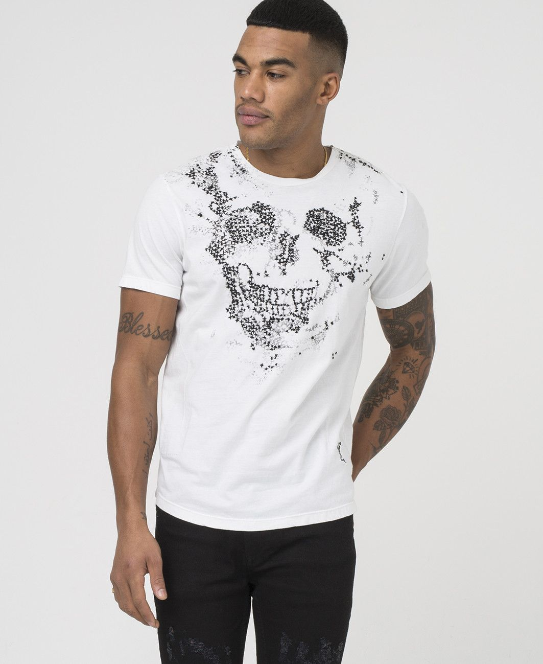 Crew neck tee with hand embroidered stitching detail on front chest,  contrast skeleton branding at hem, and curved hem.