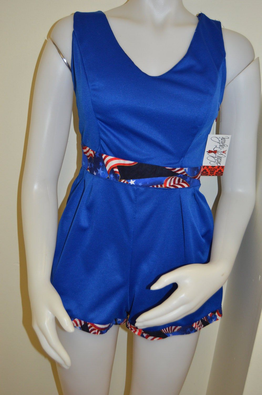 Patriotic pin up romper! Royal blue sleeveless romper criss-cross back with red, white & blue flag print accents. Cute and playful Americana #IndependenceDay #royal #flag #July4th #romper #summer #MemorialDay #patriotic #OpenBack #RedWhiteAndBlue