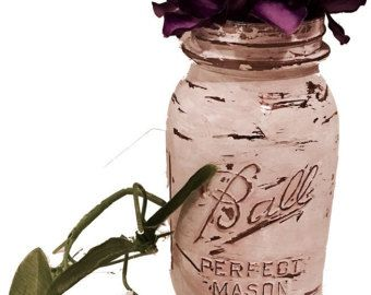 Painted Mason jar that was distressed with all natural products for a shabby chic look and then, painted with blush pink and linen white chalk paint colors with a rustic style that now makes a beautiful, flower vase or storage jar.