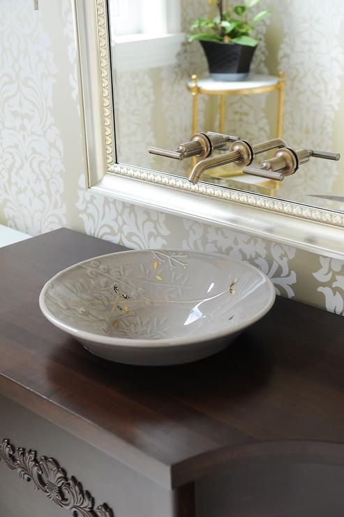 Transitional bathroom features white and gold flocked wallpaper lined with a faucet lining a silver leaf beaded vanity mirror above the round gray bowl sink atop the curved wood washstand.