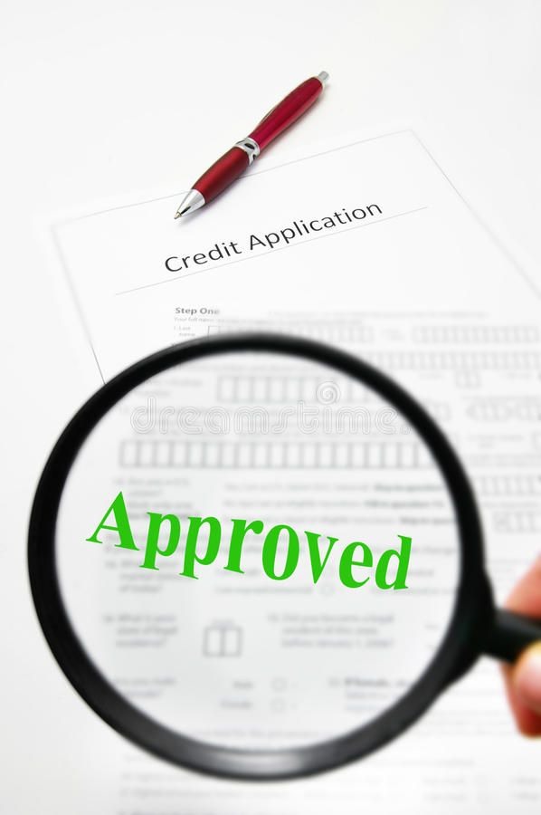 Approved credit. A credit application and magnifying glass