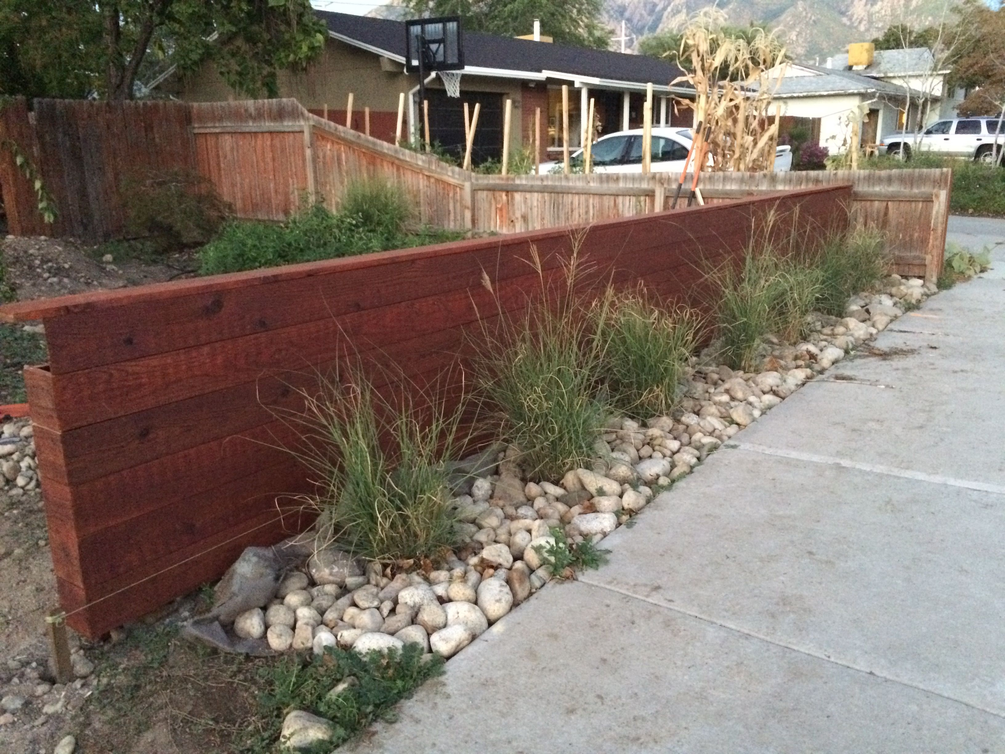 Horizontal privacy fence with granite cobble and fountain grass to complement