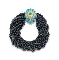 ONYX AND TURQUOISE BRACELET, BY CARTIER Formed of a twist of eleven rows of onyx balls, the dome-shaped clasp punctuated with turquoise cabochons, circa 1950, 18 cm., Gross weight: 65.43 gr., 18K yellow gold setting (750), French punches Signed Cartier Paris