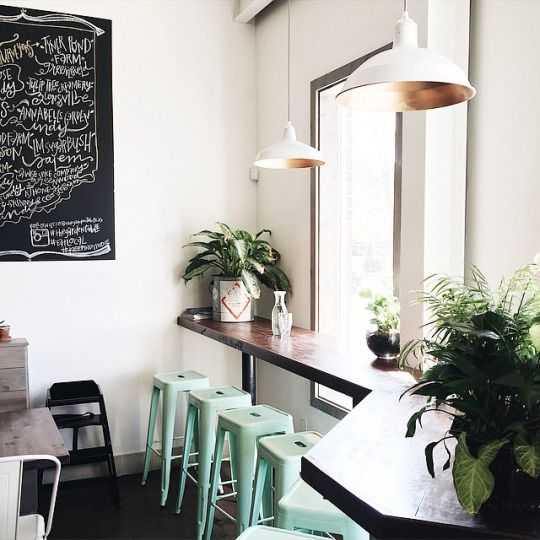 i like the mint green stools with the dark wood counter in this cafe coffee shop also the chalkboard art and the morning light