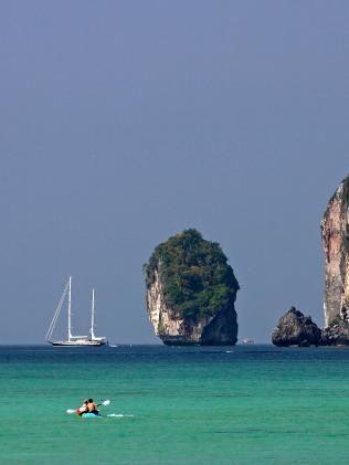 Large cruising ketch anchored off Ao Lo Dalam beach and two kayaks Phi Phi Island Thailand