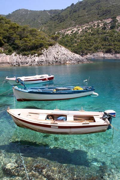 Fishing boats on crystal clear waters, Zante island in Greece.
