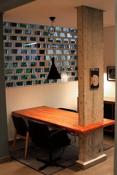 Sala de jantar com mesa em madeira Ipê engastada no pilar de concreto aparente. Pilar descascado. Aparador de apoio revestido em folha de madeira e portas de correr revestido em fórmica. Decoração com quadros. Pendente sobre mesa de jantar.
