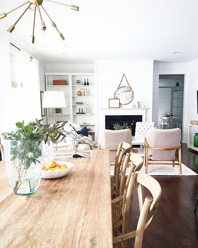 living + dining minimalistic trendy dining room and living room. Long light wood table, light pastel pink arm chairs, bohemian mirrors