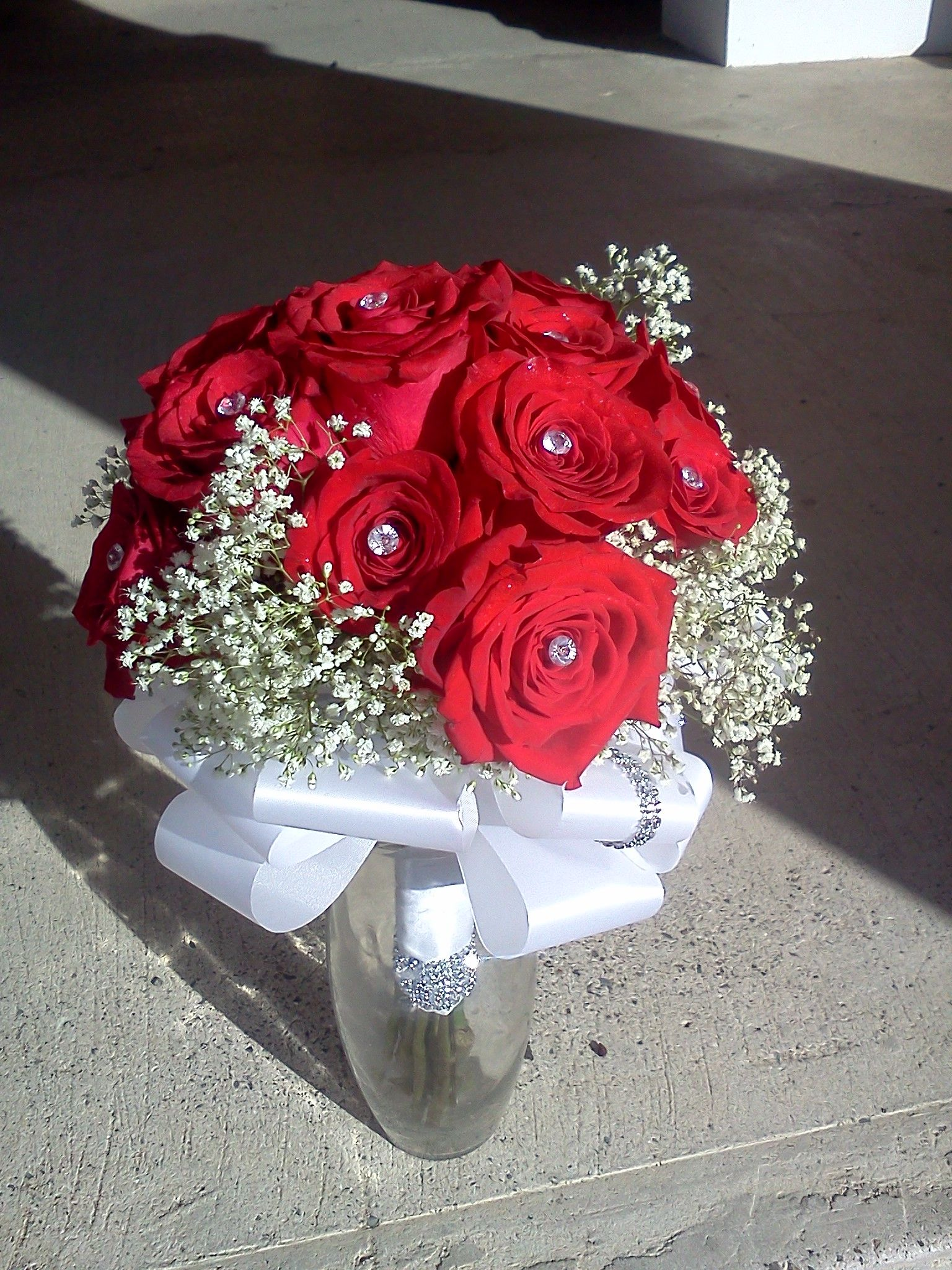 Red rose bridal bouquet with diamond head pinswhite ribbon and