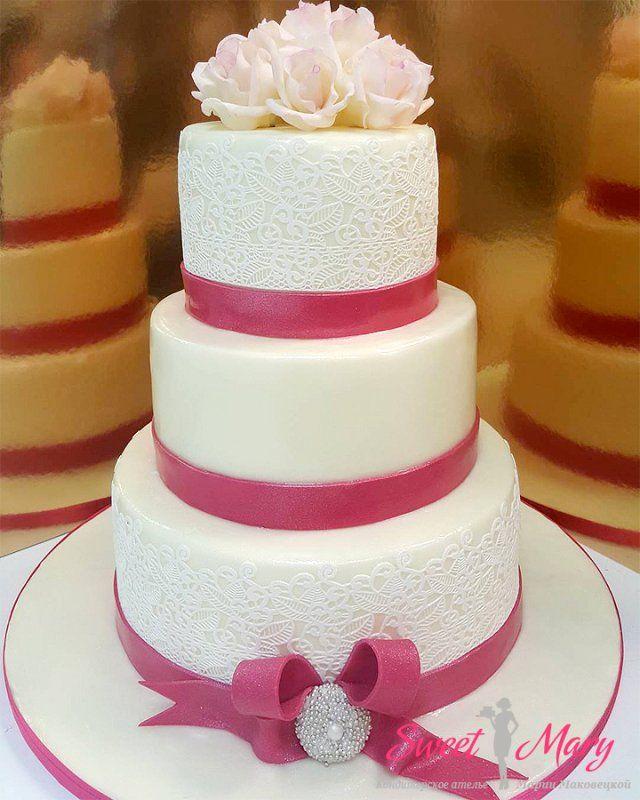 Превосходный торт для свадьбы — 3 яруса, покрытие белой мастикой, отделка красными лентами и цветочной композицией. На свадебный торт нанесены узоры, имитирующие кружево.
