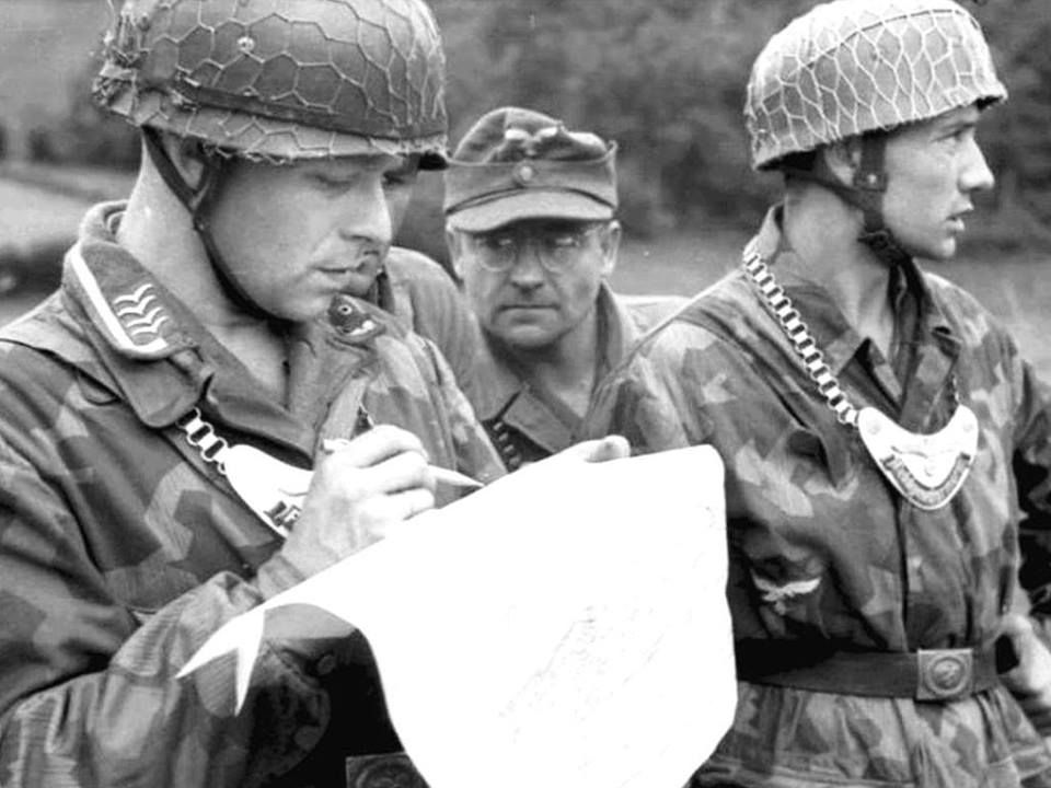 Fallschirmjäger three belonging to Feldgendarmerie, identified by its characteristic metal necklace await official indications that inspects a map carefully.