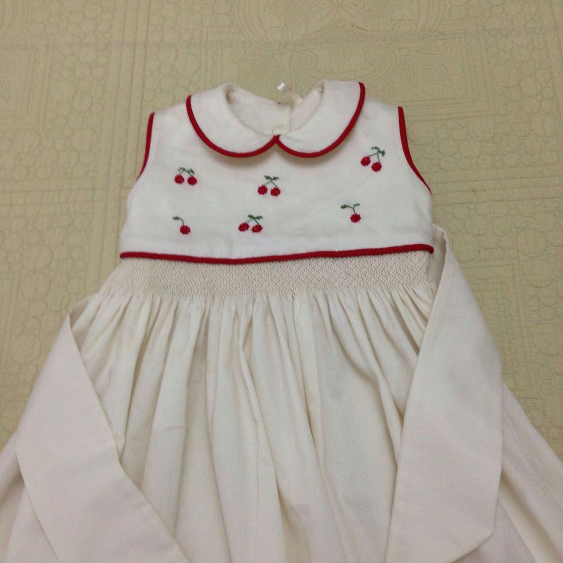 Vestidito de pique beige con bordado de cerezas en punto de cruz y bordado de nido de abeja en la cintura