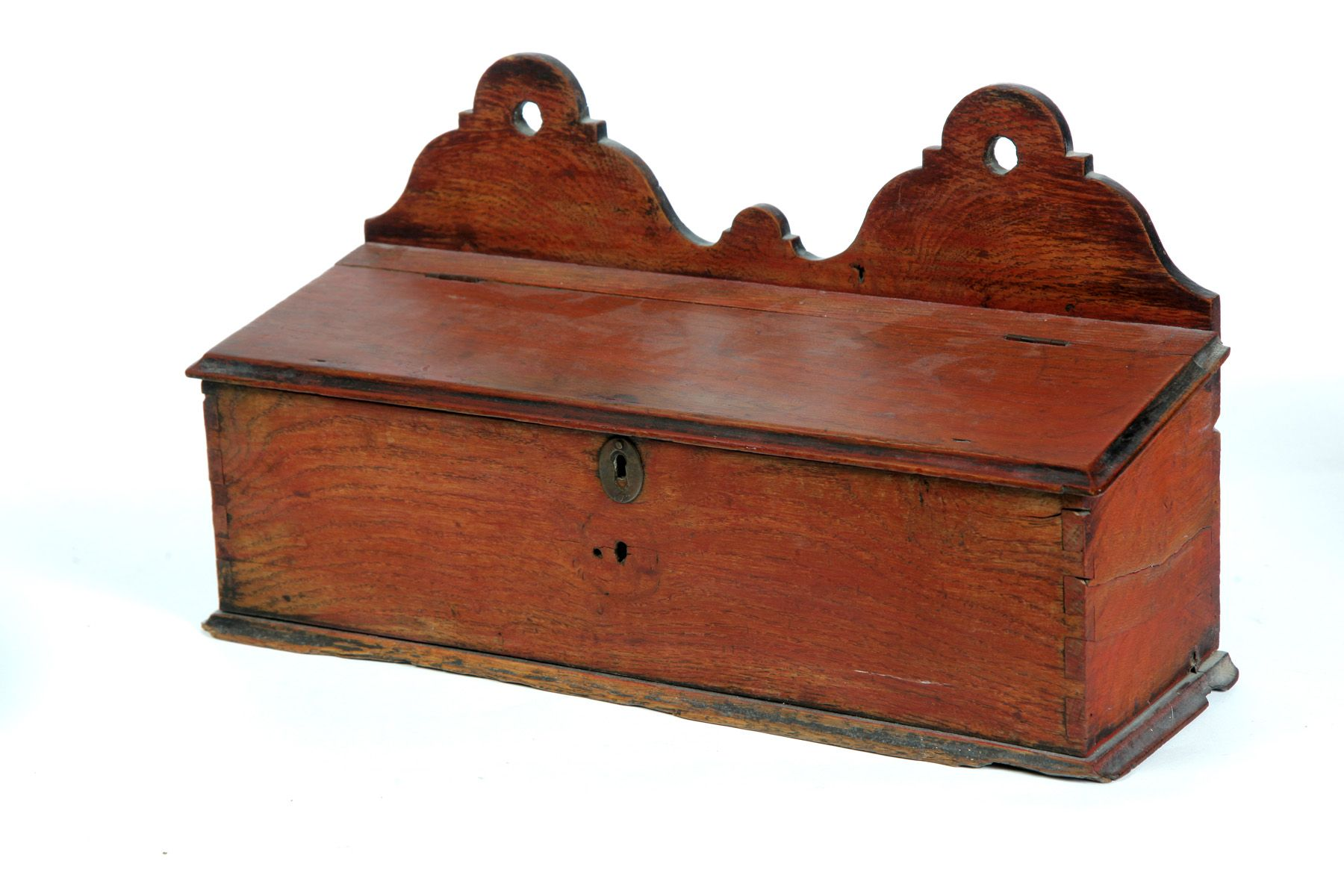 "AMERICAN HANGING CANDLE BOX.  Mid 19th century, chestnut. Dovetailed with molded bottom board and shaped crest. Slant lift lid. Old worn red paint. Imperfections. 9.5""h. 16.25""w. Ex Margaret Brusher (Michigan).  Estimate $ 100-300"