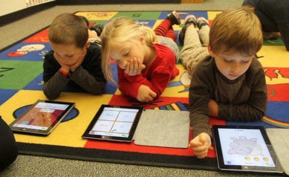 Kindergarten students play learning games on the iPad during class ...