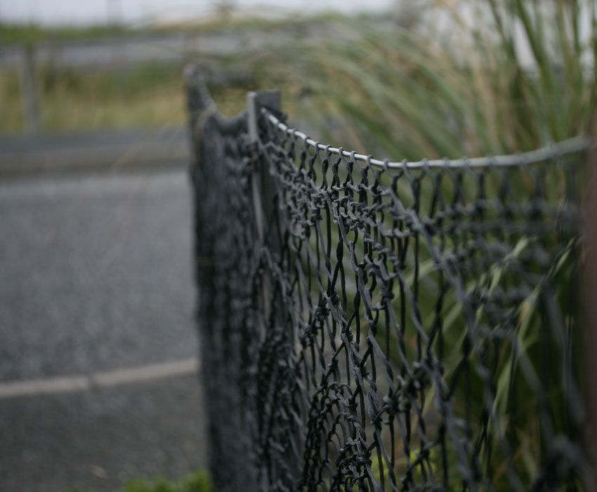 Lace knitting fence, fashioned from strong black twine (the same kind that is used to make fishing nets) by Anne Eunson. (in Hamnavoe, Burra - Shetland Islands)